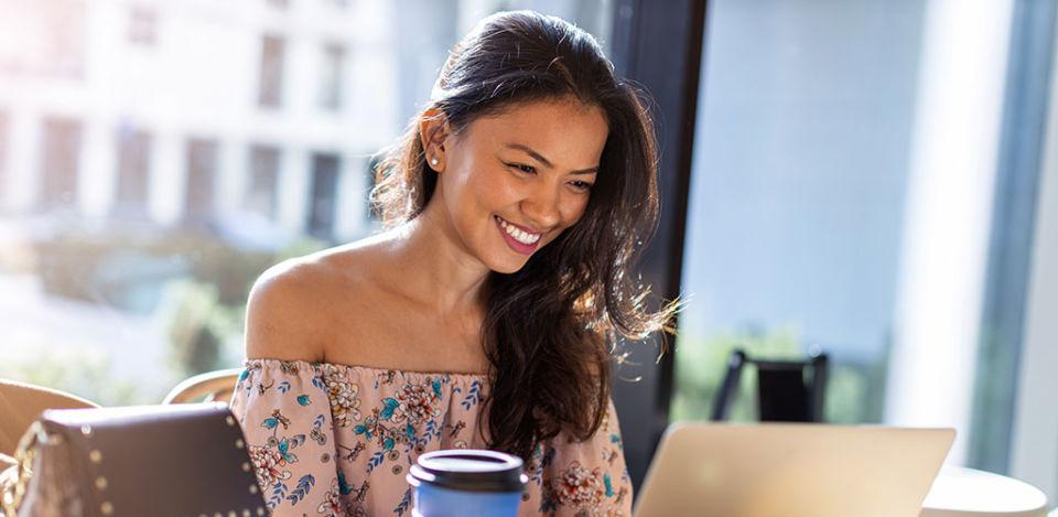 Beautiful Filipino woman using laptop at cafe