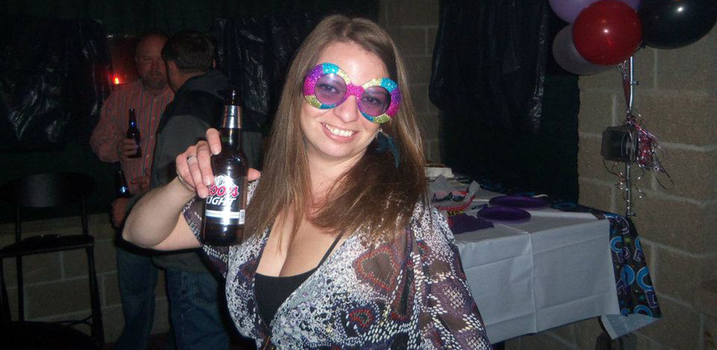 A woman with a beer and fun glasses at Last Chance