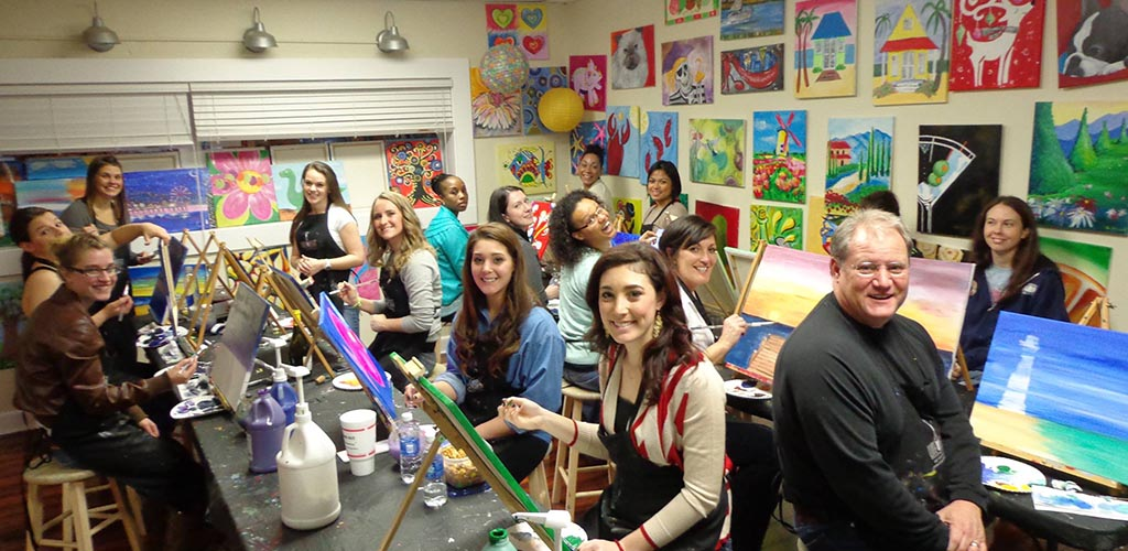 Women in a painting class at Wine and Design