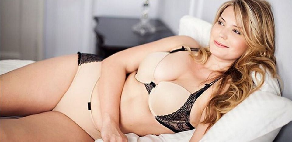 BBW cougar smiling on a bed