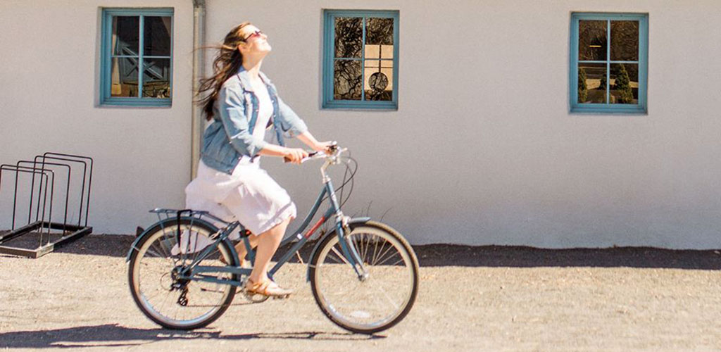 A woman riding her bike in the grounds of Los Poblanos Historic Inn and Organic Farm
