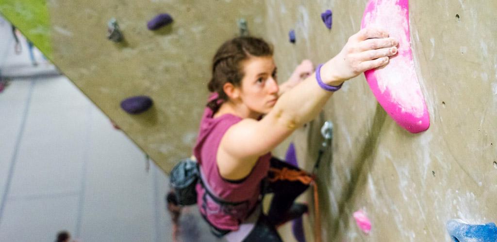 An attractive woman climbing the wall at Climb Nashville