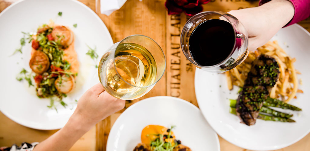 Toasting with wine over delicious dishes at Robust Wine Bar & Cafe
