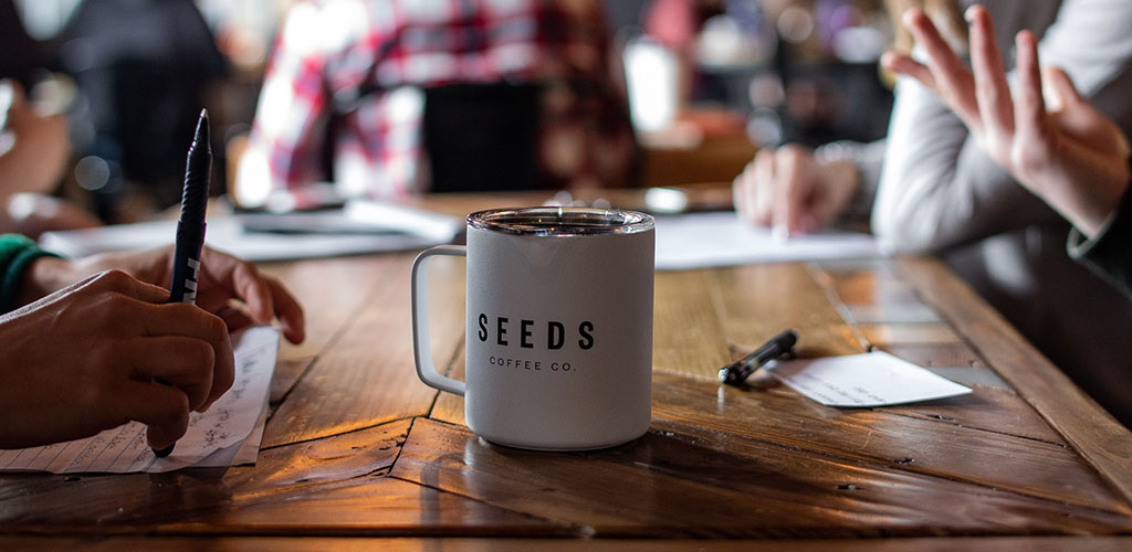 Coffee from Seeds Coffee Co. in the middle of a meeting table