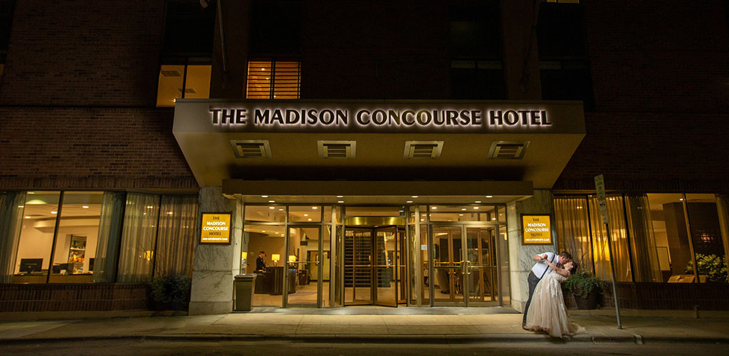 Exterior of The Madison Concourse Hotel and Governor's Club with a couple kissing