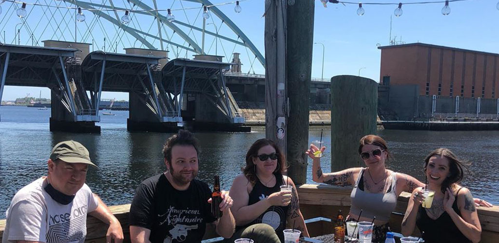 Friends hanging out by the harbor at The Hot Club