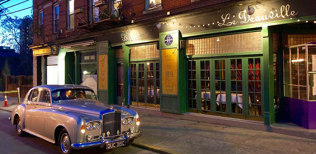 Le Deauville at night with a vintage car parked out front