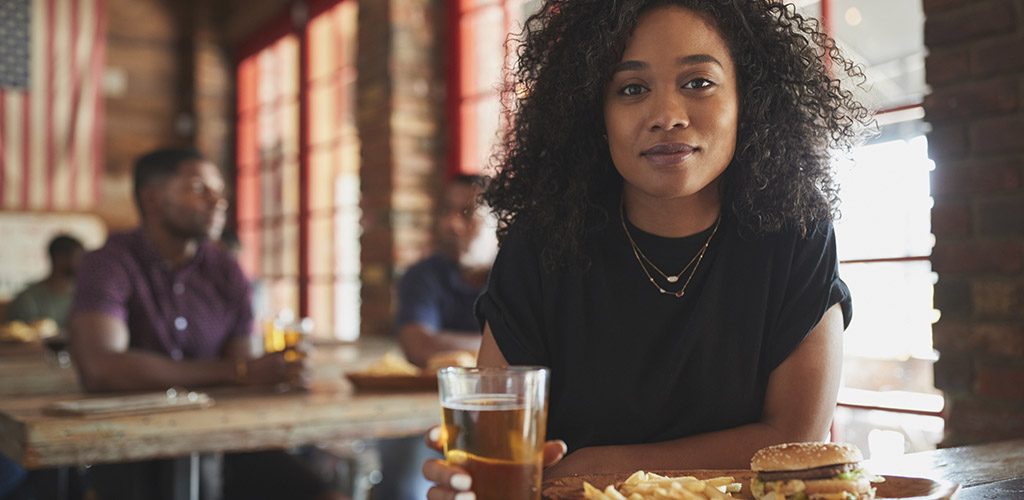 A beautiful woman with a beer and burger