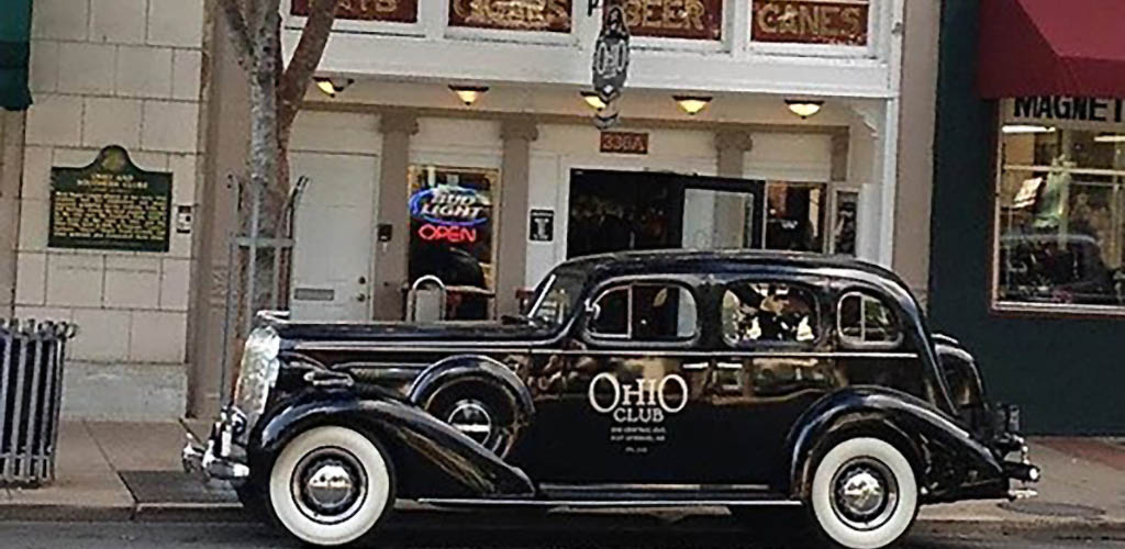 A vintage car parked outside of Ohio Club