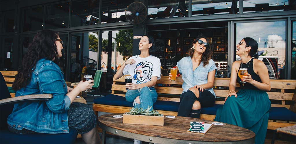 Group of women chatting at a wine bar