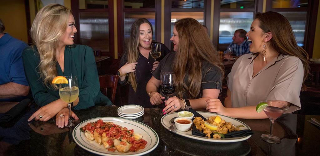 A woman running into her friends at Amerigo Italian Restaurant