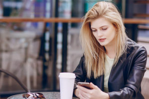 Blonde woman in Chandler Arizona using a dating app at a table