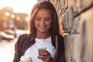 Woman using a dating app in Paterson New Jersey with coffee in hand