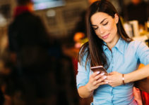 Brunette in blue blouse using a dating app in Winston Salem