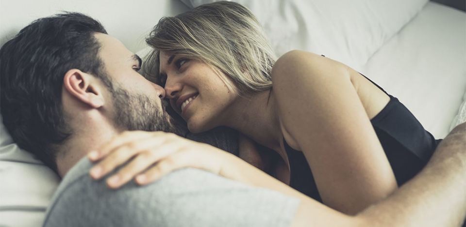 Confident man in bed with a woman