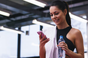 Brunette woman with a towel looking at her dating app while working out
