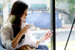Woman using a Preston England dating app while drinking coffee