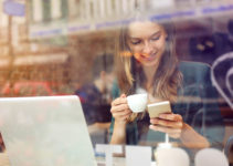 Crawley England woman playing with a dating app while drinking coffee