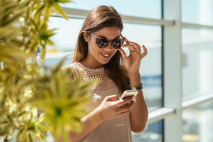 Miami dating app being used by a woman by a window