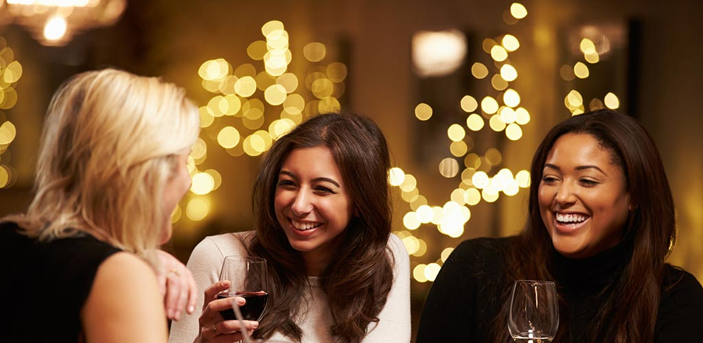 Three single women drinking wine and looking for Buffalo New York hookups at a bar