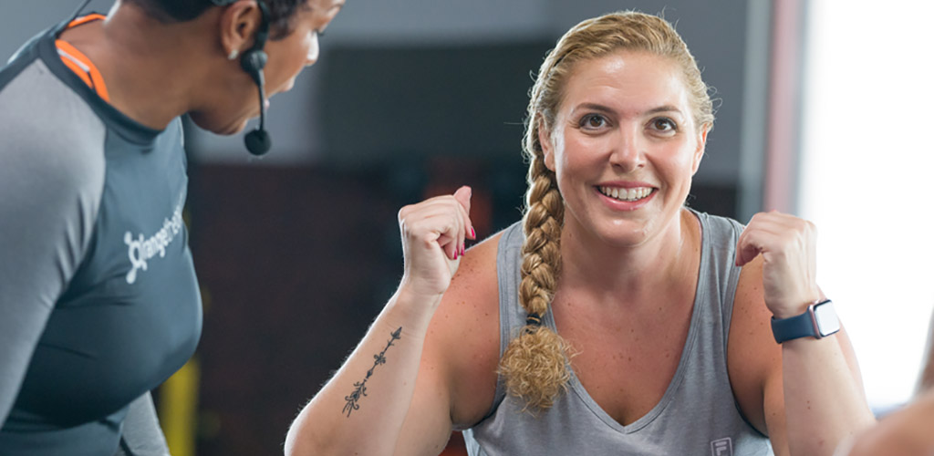 A curvy woman in a workout session at Orangetheory Fitness