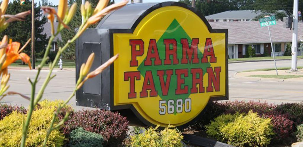 Big yellow subway-shaped sign with green diamond in center and Parma Tavern written in capitals in red centered over top