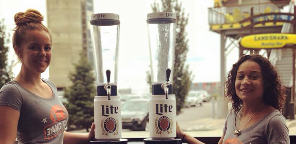 Two pretty servcers at Big Bang carrying cool Miller Lite draft pints