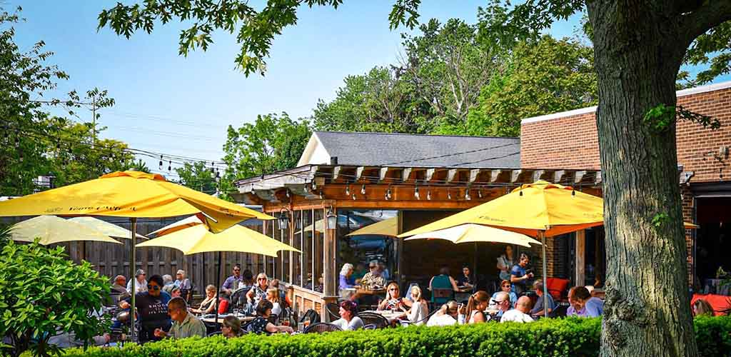 A sunny patio with yellow umbrellas at Wine Bar Rocky River with lots of young people having fun