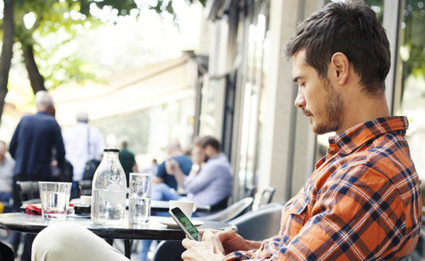 Man in a cafe learning how to respond to an ex asking how you are