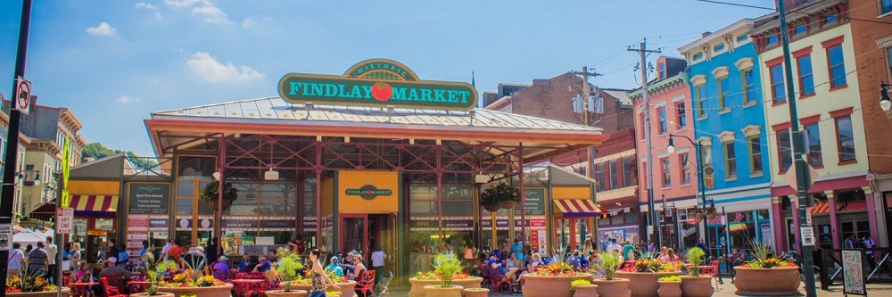 Outdoor setting of Findlay Market with small crowds at tables and lots of potted plants
