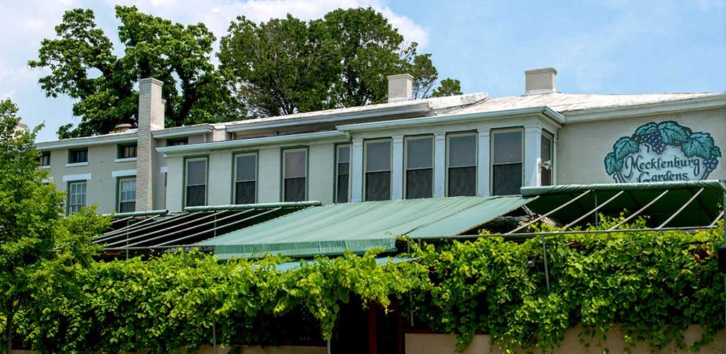 Windows and awning over a hedge row in front of a restaurant