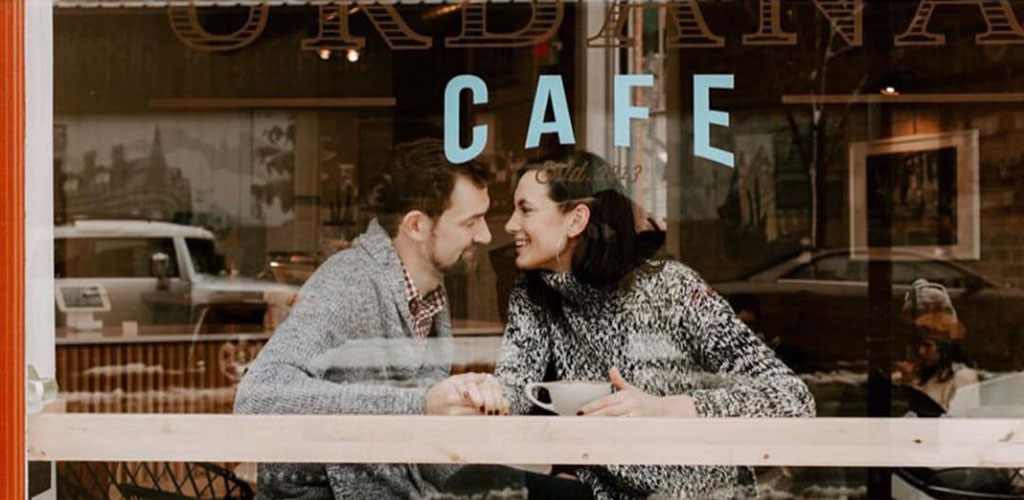 A young couple laughing intimately in a cafe window with the words CAFE over their heads