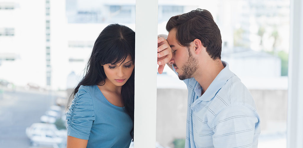 sad man and woman with wall between them wondering how to know when their relationship is over