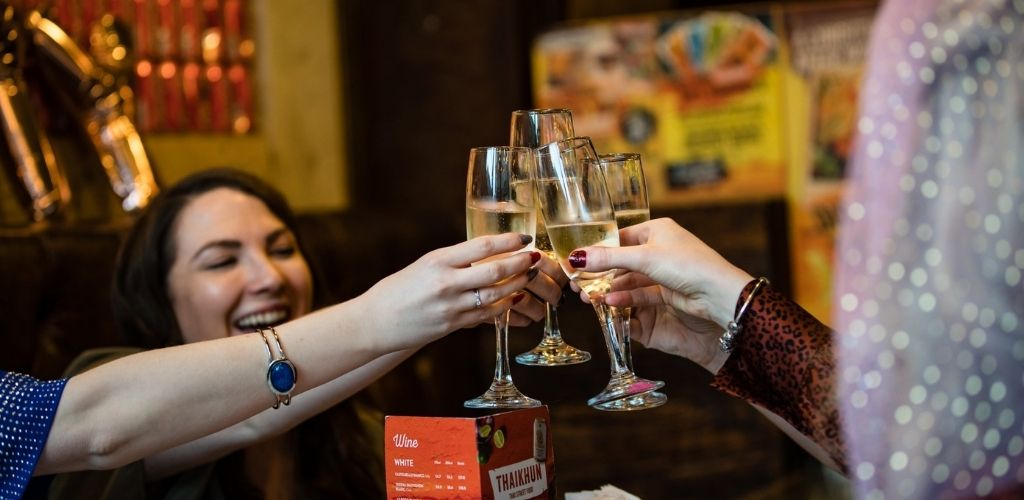 4 Liverpool singles celebrating and raising their glasses in Thaikhun