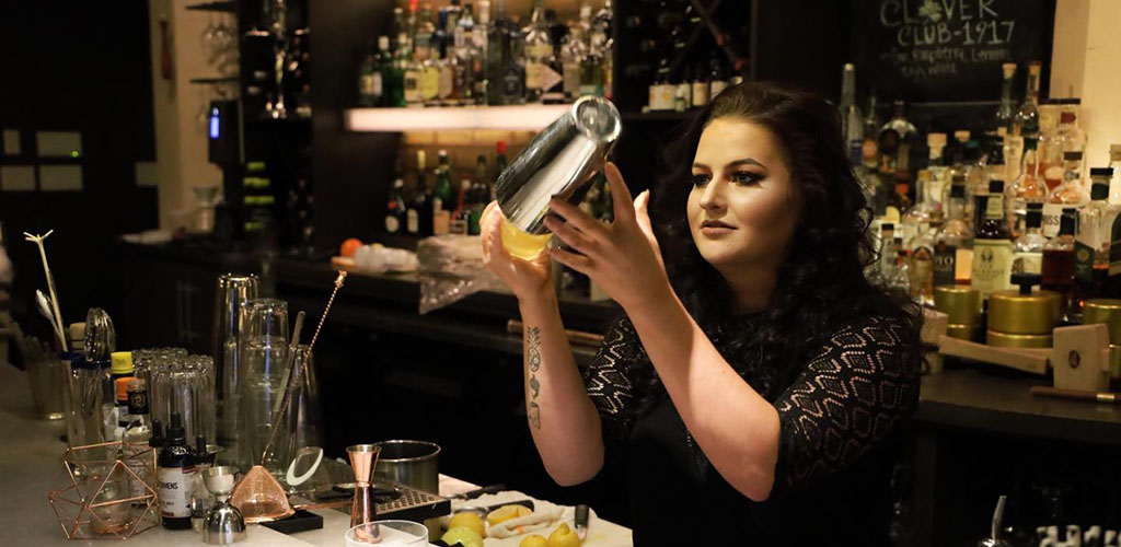 A gorgeous woman mixing drinks at Society Lounge