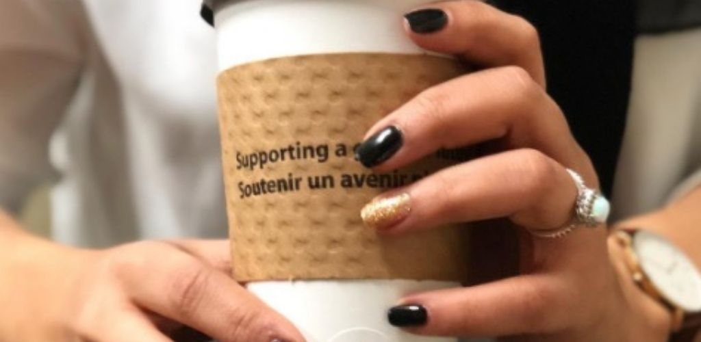 A Brampton single holding a coffee cup at Steaming Cup
