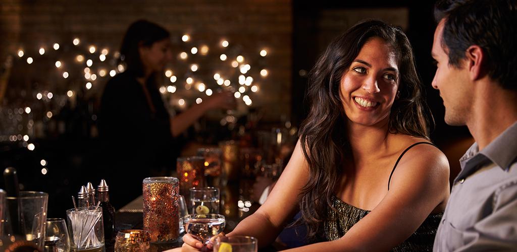 Man and woman flirting in bar and plotting Bristol hookups