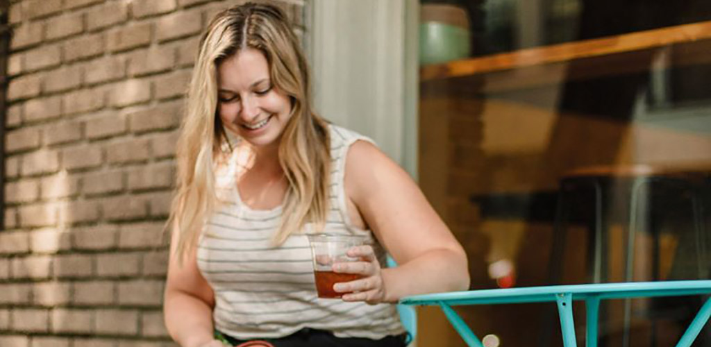 A curvy woman with iced coffee from Mammoth Espresso
