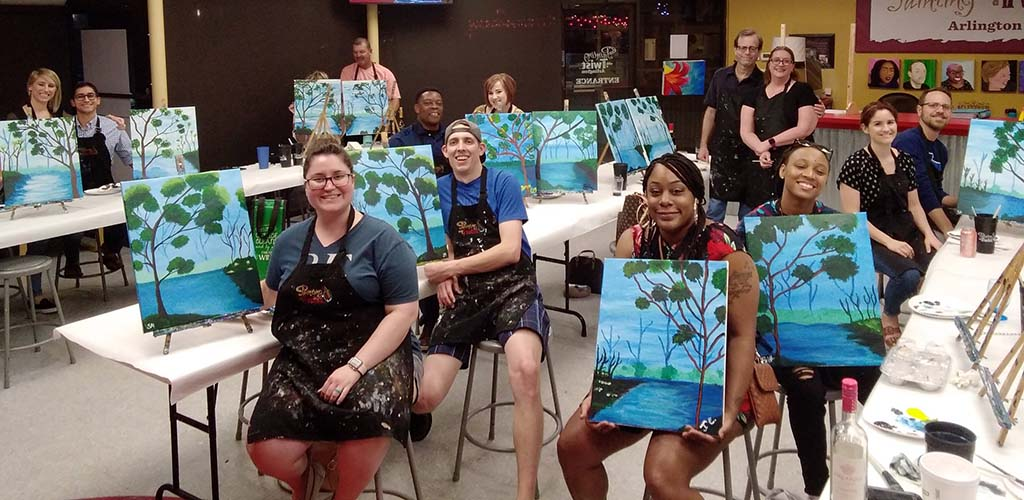 Ladies showing off their artwork at Painting with a Twist