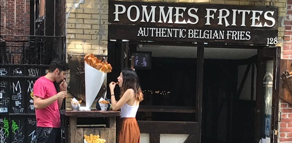 A young man and woman in front of Pommes Frites