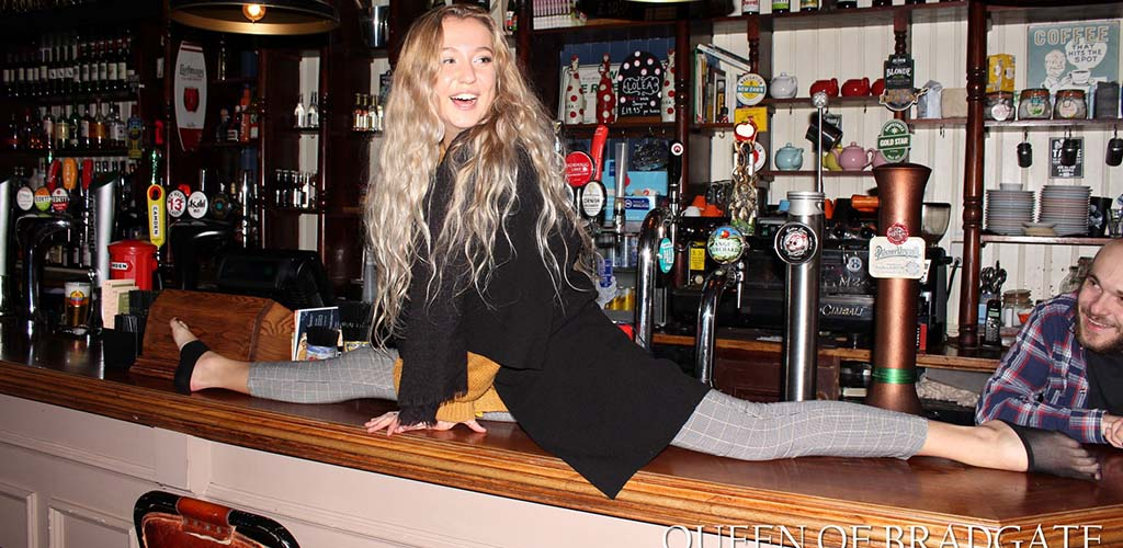 A woman doing the splits on the bar in Queen of Bradgate