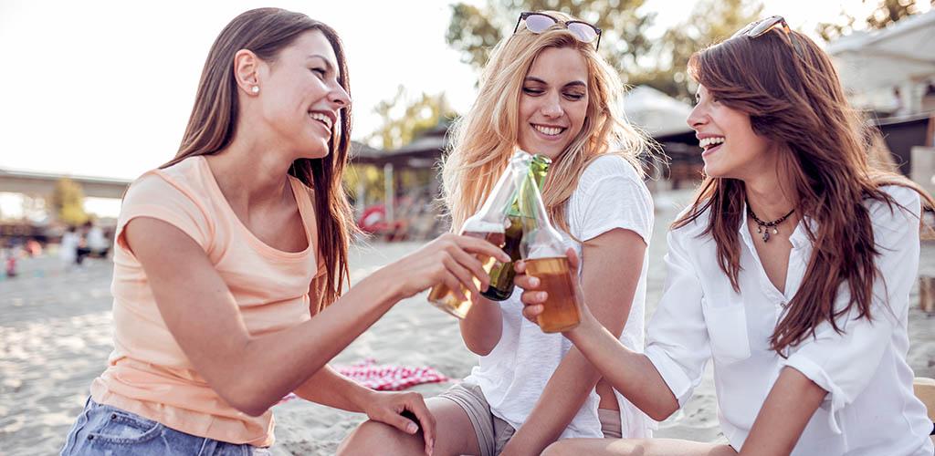 Happy Virginia Beach girls drinking beers at the beach