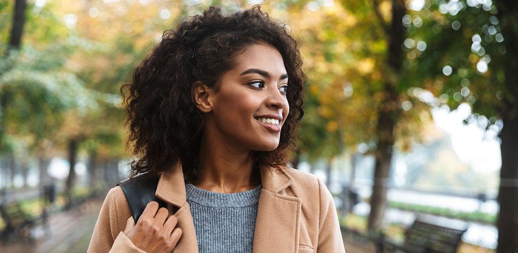 A Washington DC girl walking through a park in autumn