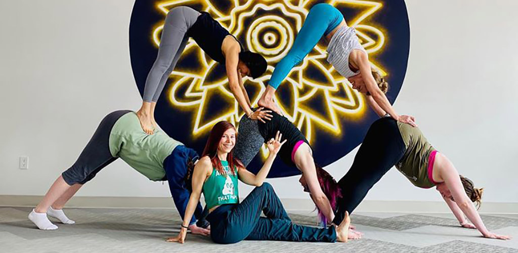 Flexible women in a complex yoga pose at Honest Soul