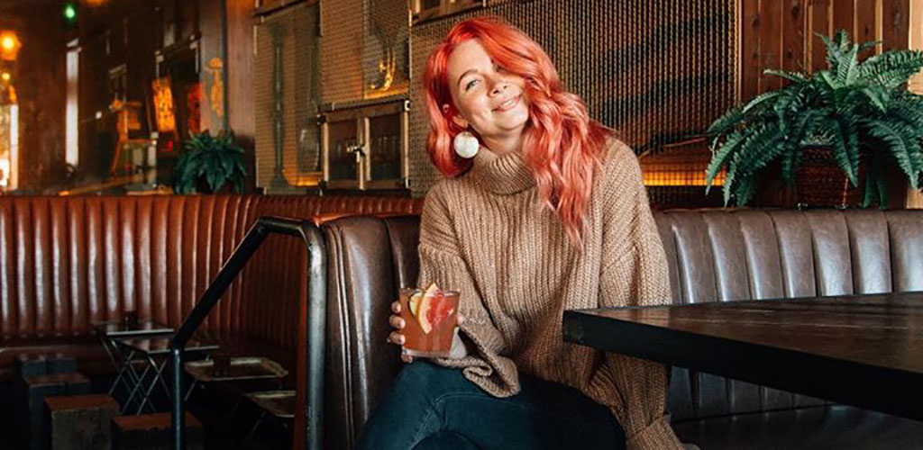 A beautiful woman with red hair holding a cocktail at Sycamore Den