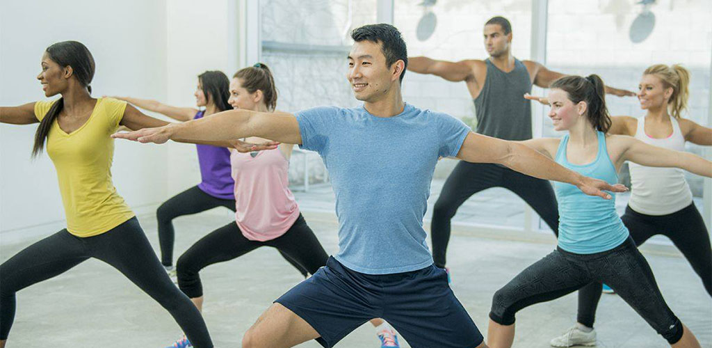 Men and women in a yoga pose at Fitness 1440