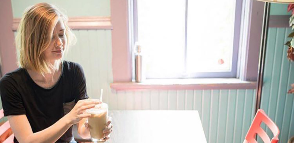 A young woman enjoying her iced coffee at Rochambo Coffee and Tea House