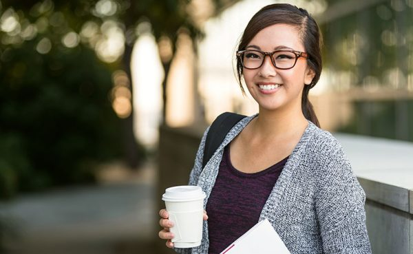 A student with a cup of coffee on the way to class