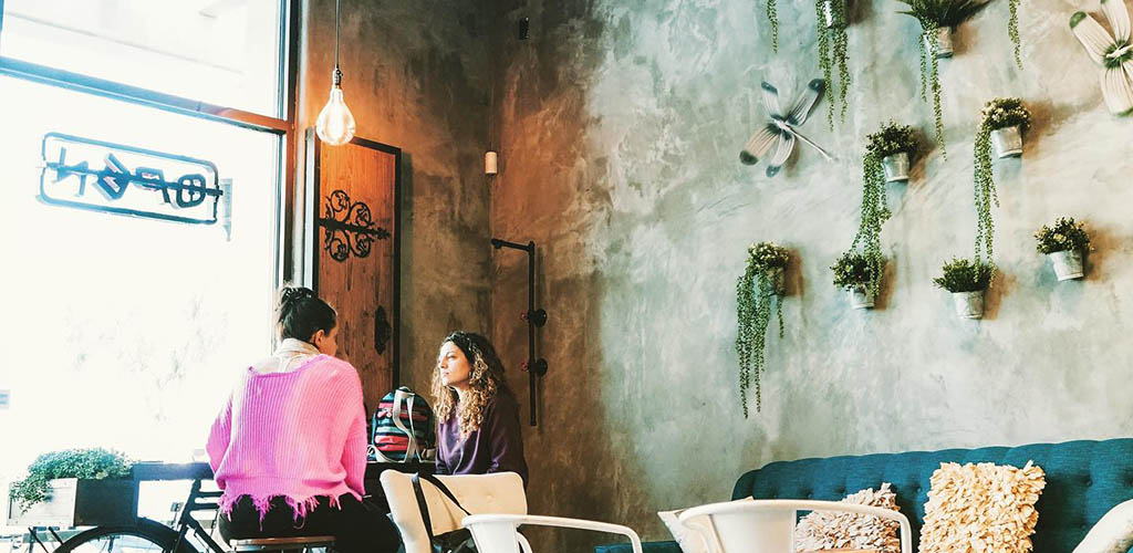 Two girls having coffee in the industrial-inspired interior of Coffee Religion