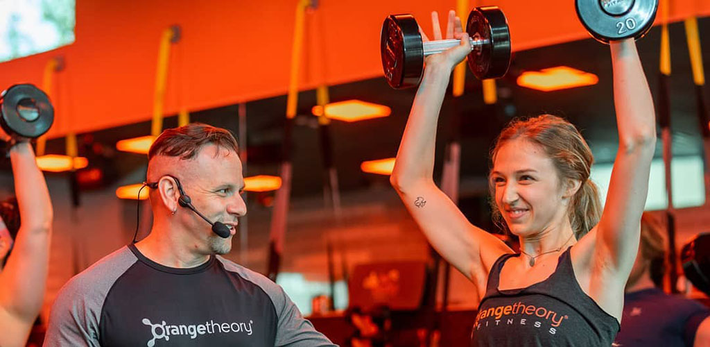Lifting weights with an instructor from Orange Theory Fitness